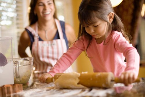 Mother watches little girl rolling out cookie dough
