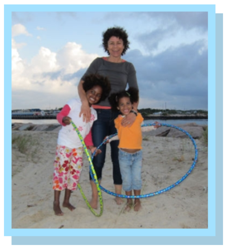 woman hugging two children holding hula hoops