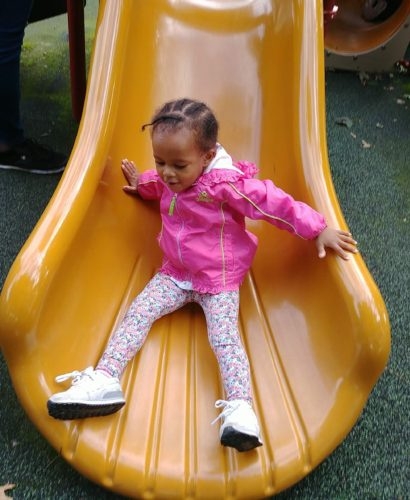 young girl in pink jacket sliding down yellow slide
