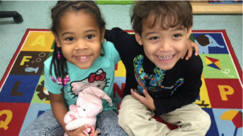 Smiling young girl and boy sit on rug at preschool