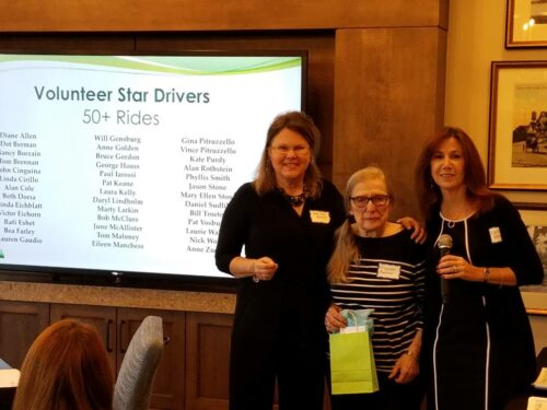 Three women stand in front of a screen that says RideConnect volunteer star drivers
