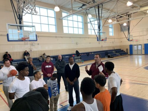 Group of youth play basketball with Isiah Thomas