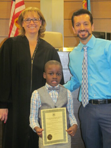 Woman judge stands with father and adoptive son who is holding a certificate
