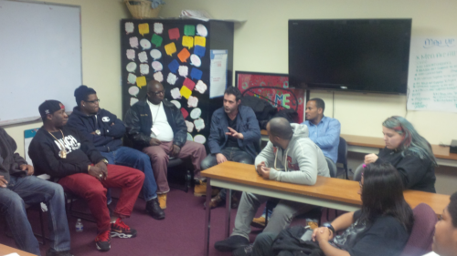 Group of young men meet with team leader in SNUG program