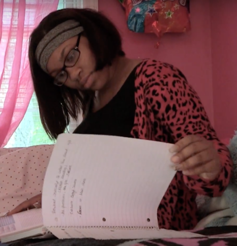 Young woman sitting in her bedroom doing her homework