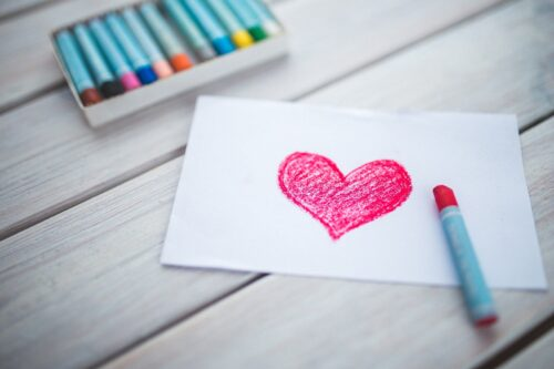 paper with a red heart drawn in crayon
