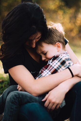 mother hugging sad little boy